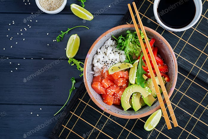 Hawaiian salmon fish poke bowl with rice, cucumber, radish, sesame seeds and lime.