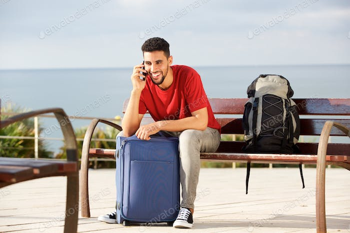 happy male traveler sitting on bench with bags and talking on mo