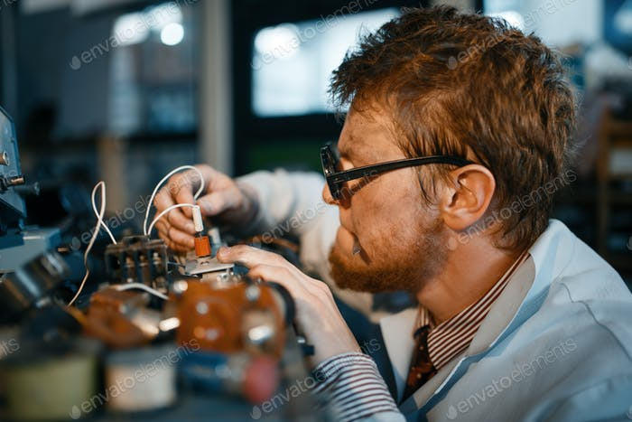 Scientist prototyping electrical device in lab