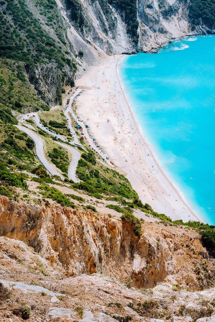 Serpentine Zickzack Straße hinunter zum berühmten Myrtos Beach. Viele Touristen am sonnigen Strand, Kefalonia