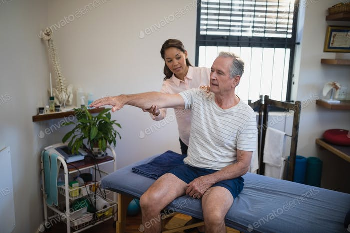 Female doctor examining shoulder of senior male patient