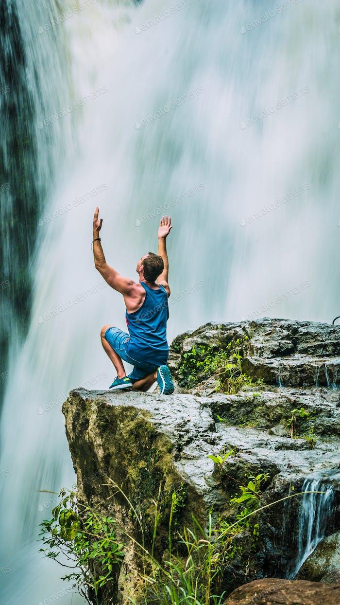 Man sitting in Front of Tegenungan Waterfall near Ubud raising hands and rhapsodize it, Bali