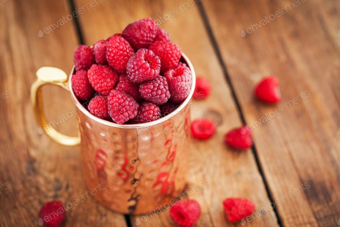 Fresh ripe raspberries in a copper mug