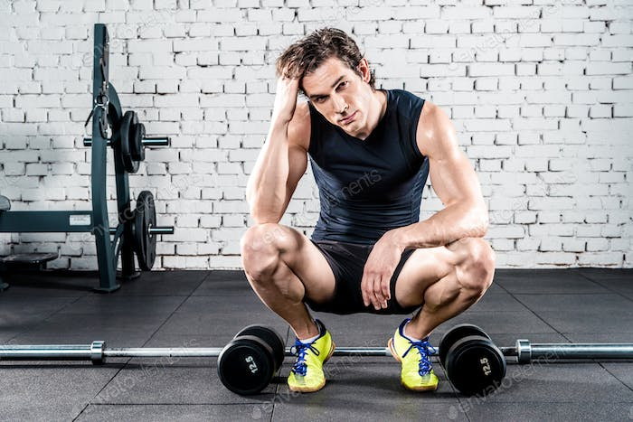 Young sportive man crouching between dumbbells in gym