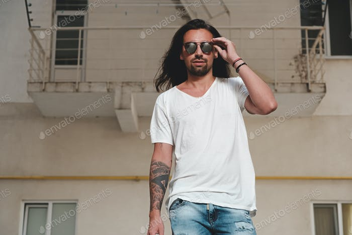 Stylish bearded man model posing with sunglasses