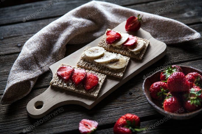 Fruity toast on wooden background. Strawberries, bread, butter and cheese.Vintage style
