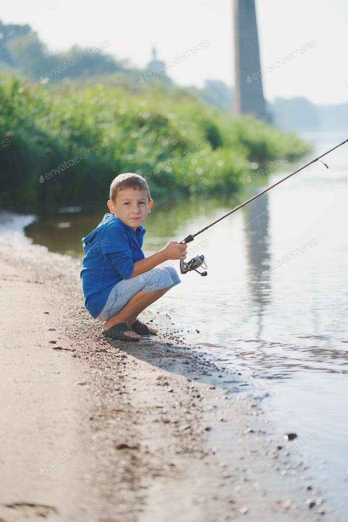 happy boy with rod on coast of river