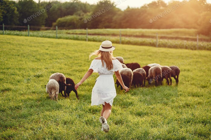 Cute girl in a field with a goats