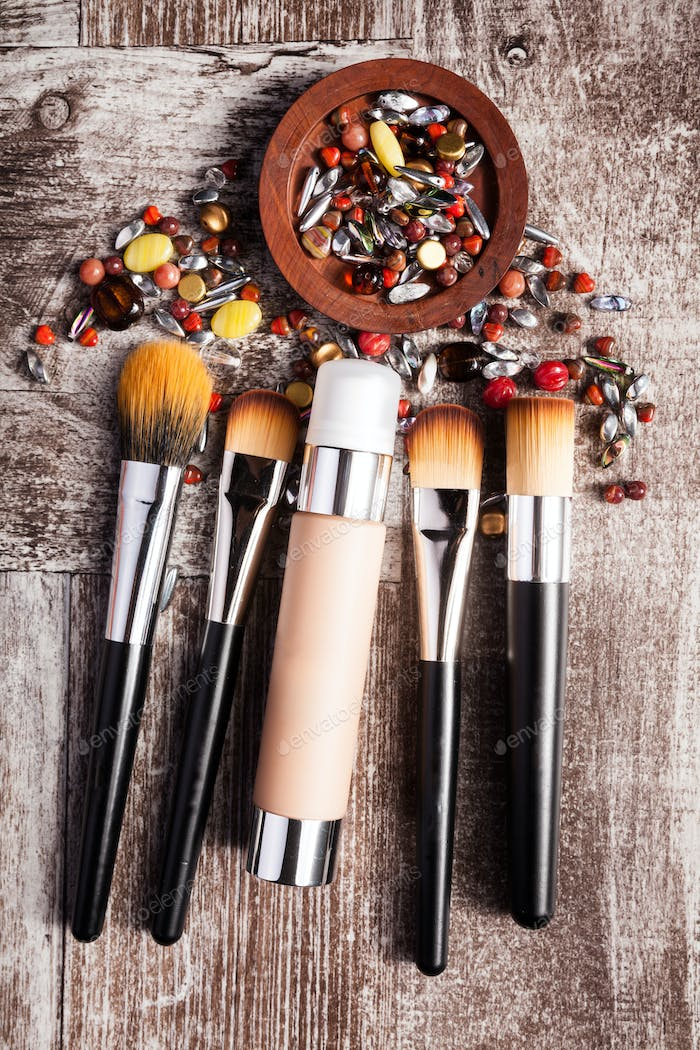 Cosmetics products and brushes in conceptual image over wooden background