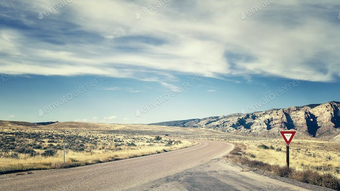 Retro color toned road with yield sign, travel concept.
