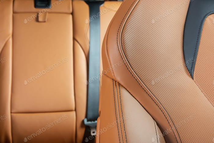Part of red perforated leather car seat with the unfocused car interior in the background