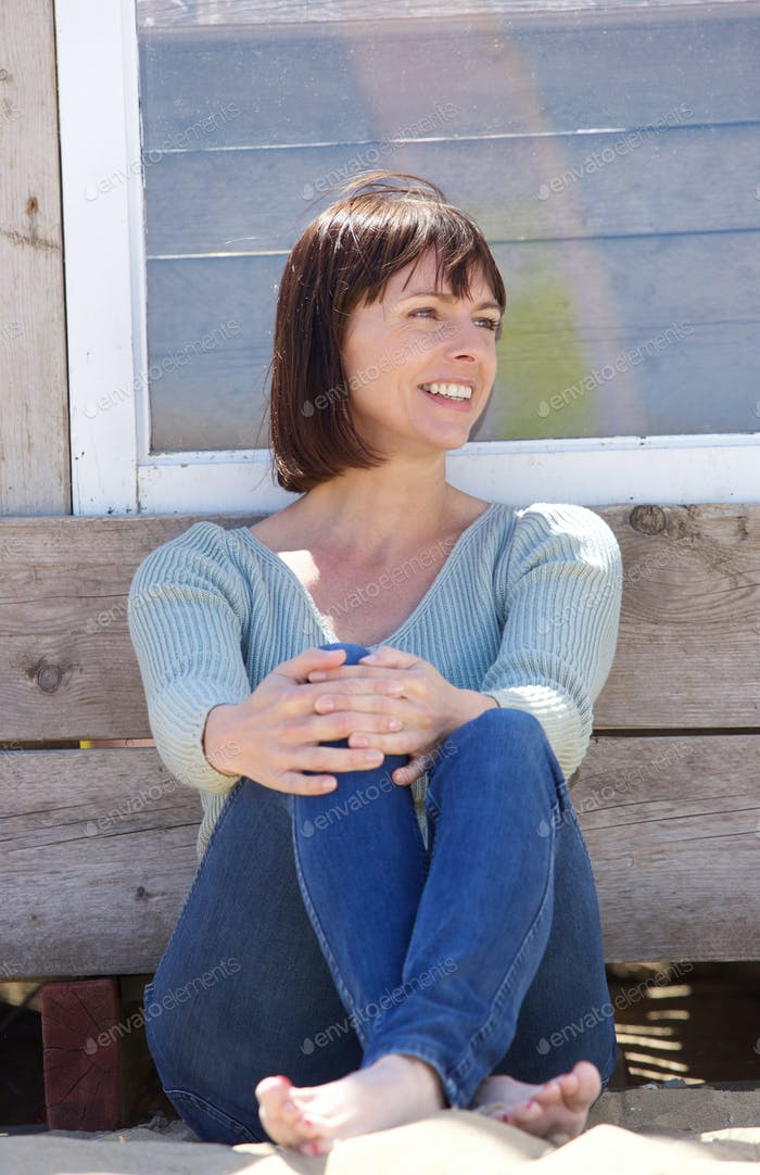 Glückliche Frau im mittleren Alter in Jeans sitzen außerhalb