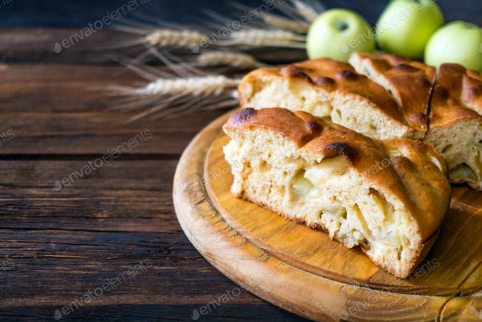 Round home-made apple pie, cobbler, brown Betty, Apple Charlotte on wooden background with apples