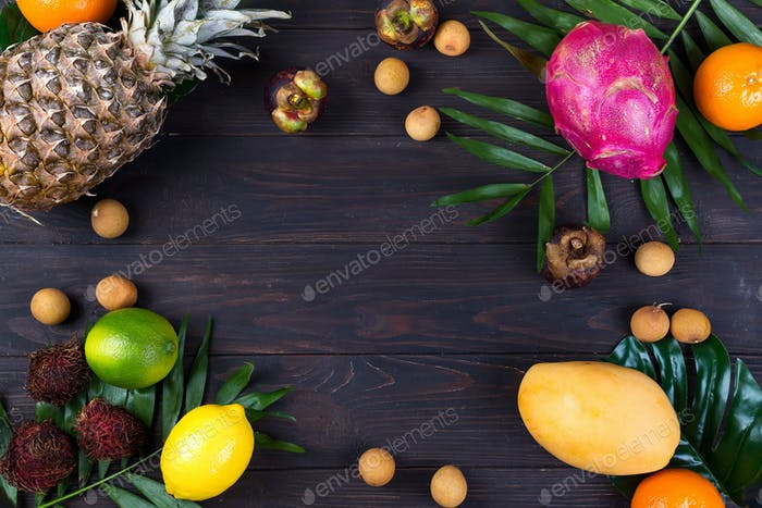 Fresh exotic fruits in a wooden box, top view with many colorful ripe fruits