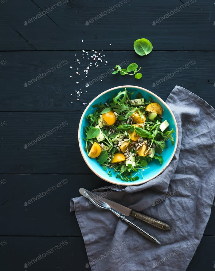 Bowl of green salad with avocado, arugula, cherry tomatoes and sunflower seeds