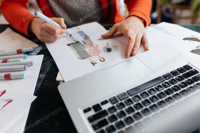 Close up woman hands drawing fashion illustrations with laptop n