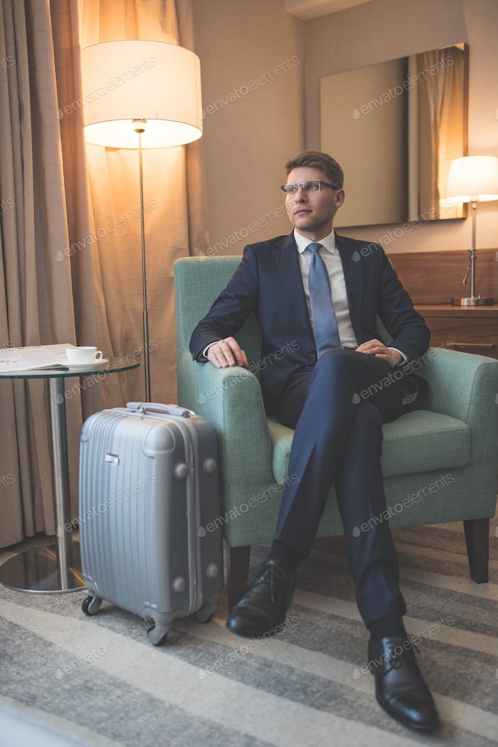 Young businessman with suitcase indoors