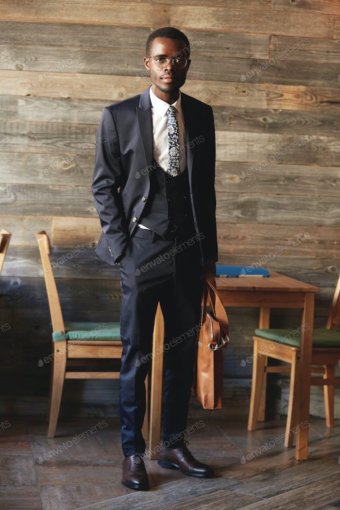 Full-length portrait of handsome African businessman wearing elegant formal suit, holding leather ba
