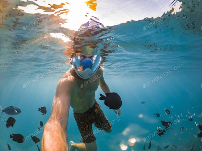 Schnorcheln in der Nähe einer tropischen Insel. Junger Mann schwimmt im Wasser. Urlaub am Meer