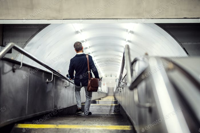 Rear view of hipster businessman walking down the stairs in subway, travelling to work.