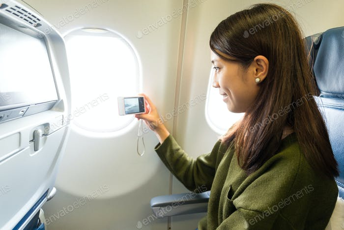 Woman taking photo out of window