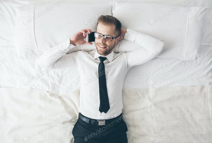 Top view. Handsome businessman with glasses lying on bed
