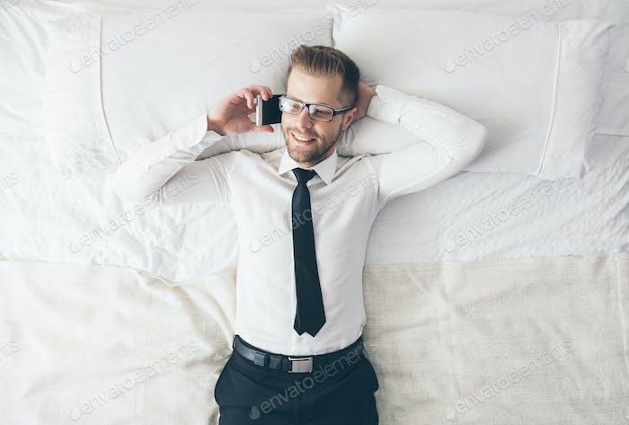 Draufsicht. Hübscher Geschäftsmann mit Brille liegend auf Bett