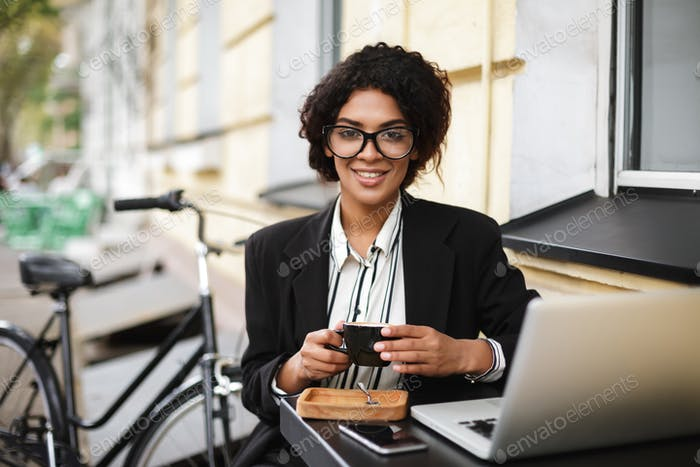 Thumbnail for African American girl in glasses sitting at the table of cafe with laptop and holding cup of coffee