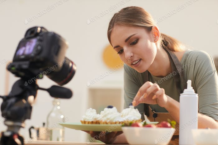 Woman shooting the process of decorating the cakes