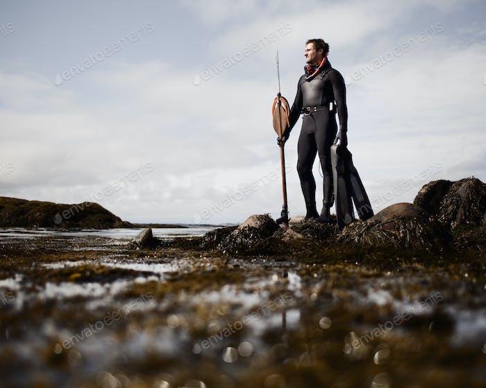 Ein Mann in einem Neoprenanzug, der am Ufer mit einer großen Speerfischer-Harpune steht.
