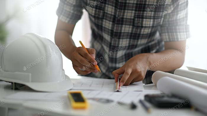 A designer is drawing for a home interior on a desk with office supplies.