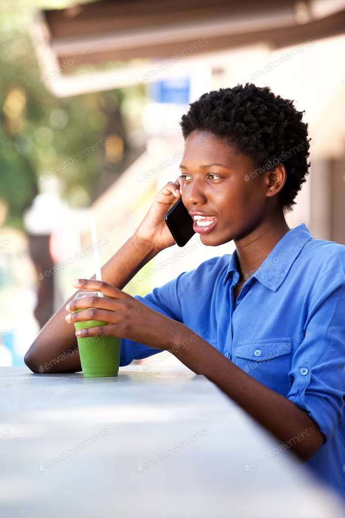 young black woman talking on mobile phone at cafe