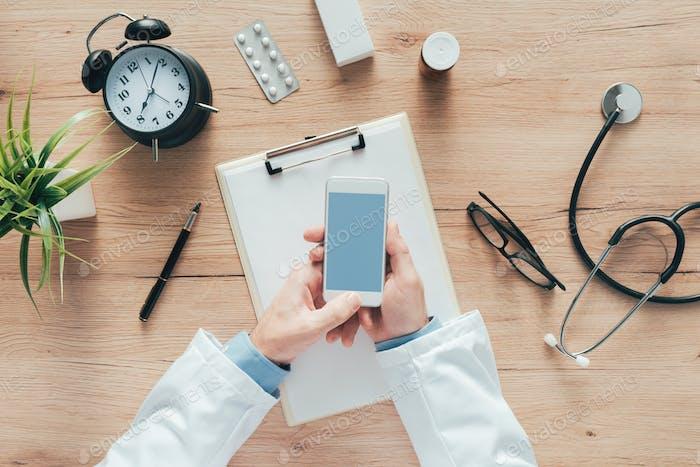 Doctor using smartphone app in hospital office
