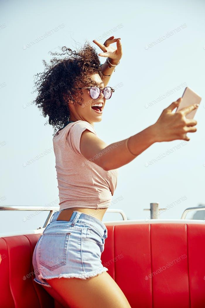 Lachende junge Frau sitzt auf einem Boot nehmen Selfies