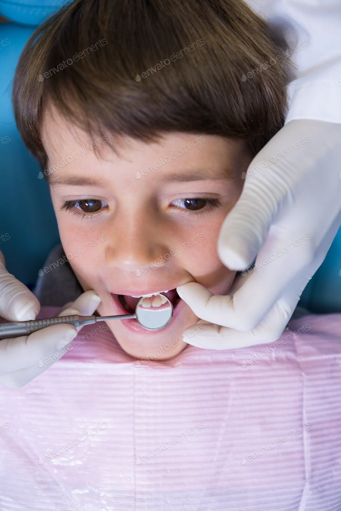High angle view of dentist holding equipment while examining boy