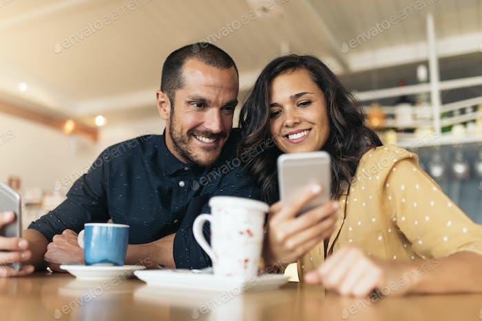 Amigos felices usando el móvil.