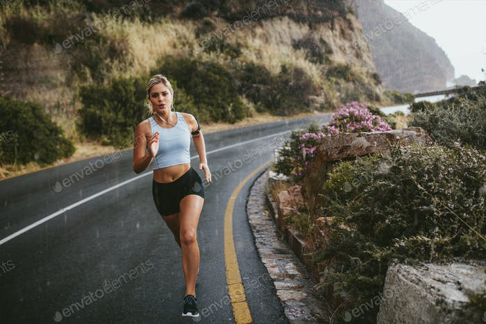 Fitness woman running on countryside highway