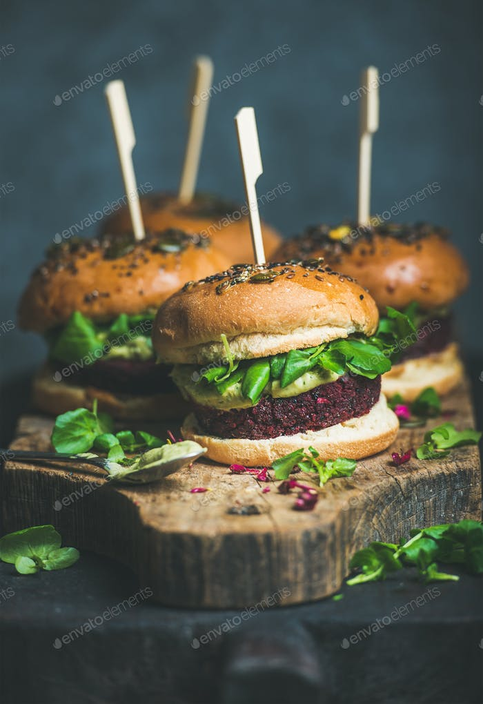 Healthy homemade vegan burger with beetroot-quinoa patty, arugula, avocado sauce