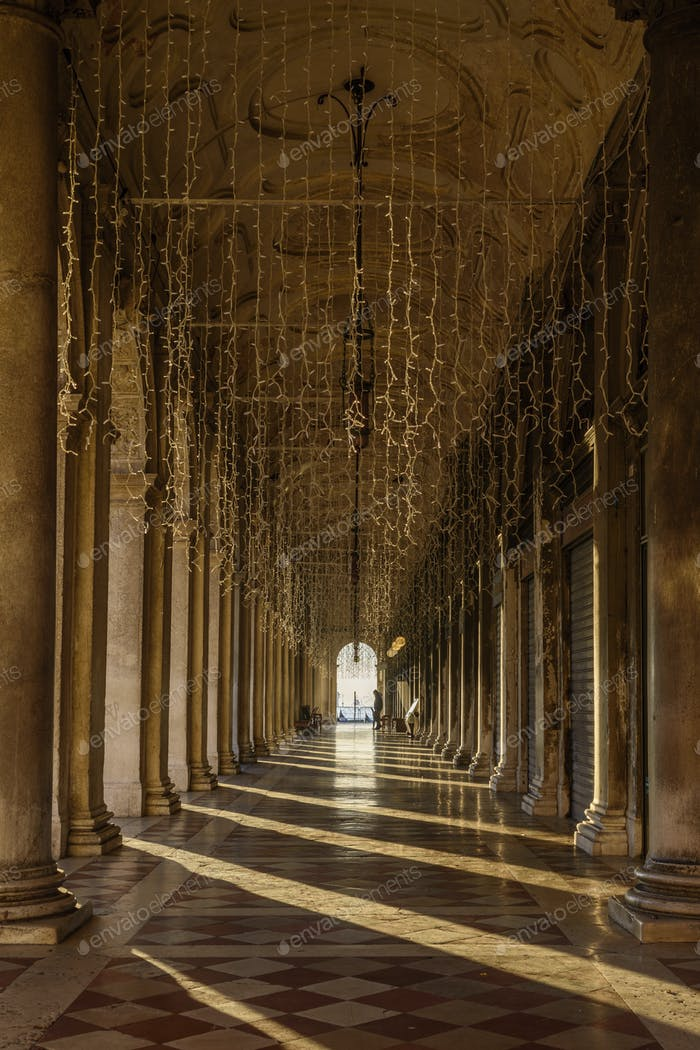 Colonnade near St Mark's Square, Venice, at sunrise. Silhouettes of people, Silhouette of a large