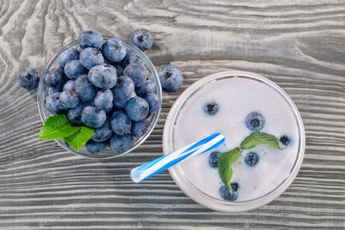 Berry smoothie or yogurt in glass and blueberries in bowl on wooden table
