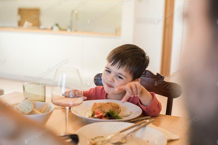 Familia joven con un niño pequeño sentado juntos para el almuerzo