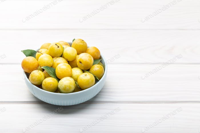 Yellow plum mirabelle fruit in bowl on white wooden table