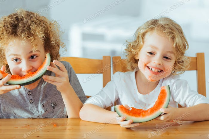 Happy brothers eating watermelon
