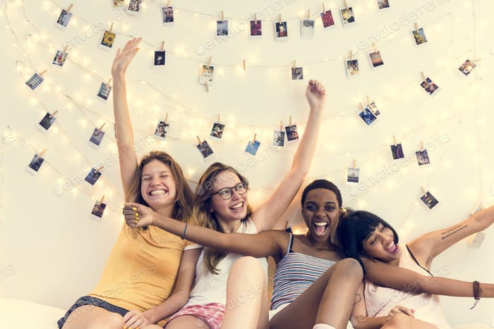 Group of diverse women sitting on bed together