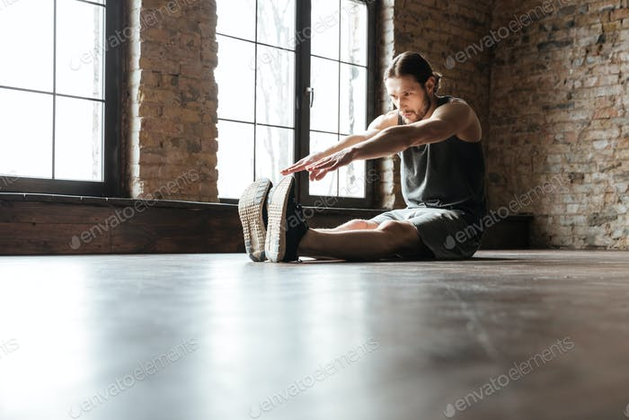 Portrait of a healthy sportsman doing stretching exercises
