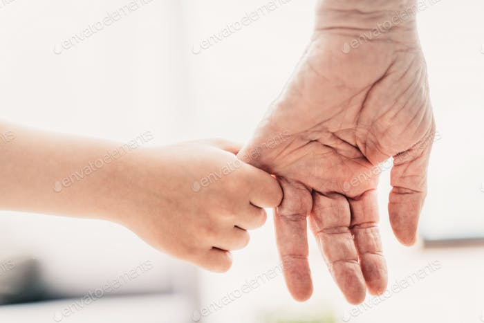 Grondson holding hand of his grandfather