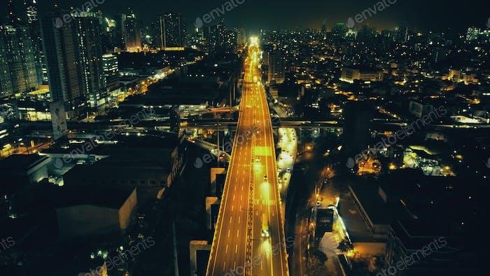 Nachtbeleuchtetes Stadtbild mit Verkehrsautobahn an der Antenne des Geschäftszentrums. Dämmerung Stadt Neonlicht