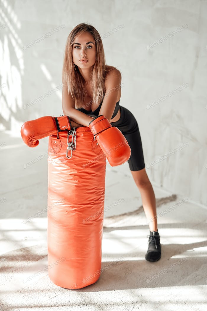 Hot girl in a black tracksuit with a punching bag and boxing gloves