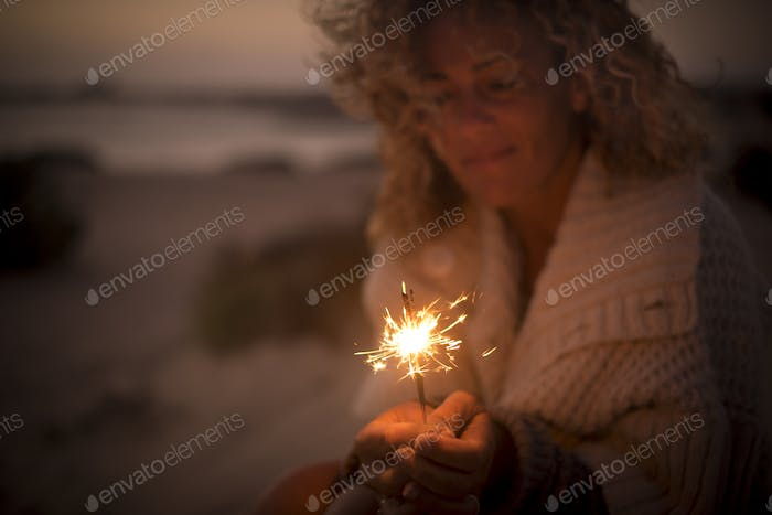 beautiful lady use and look a sparkly fire light in a summer night