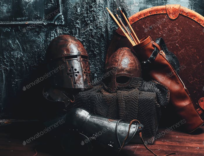 Still life with ancient shield, two rusted helmets, quiver of arrows